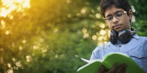 Teenage boy reading a book in nature